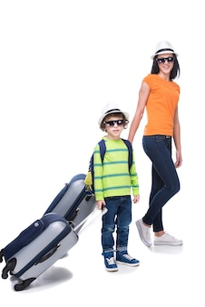 Young boy and his mother with suitcases before travel.