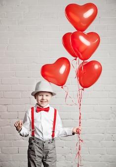 하트 모양의 ballon 들고 어린 소년
