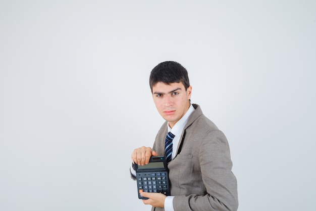 Young boy holding calculator in formal suit and looking confident , front view.