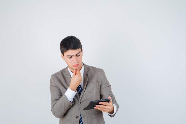 Young boy holding calculator, putting hand on chin in formal suit and looking pensive , front view.