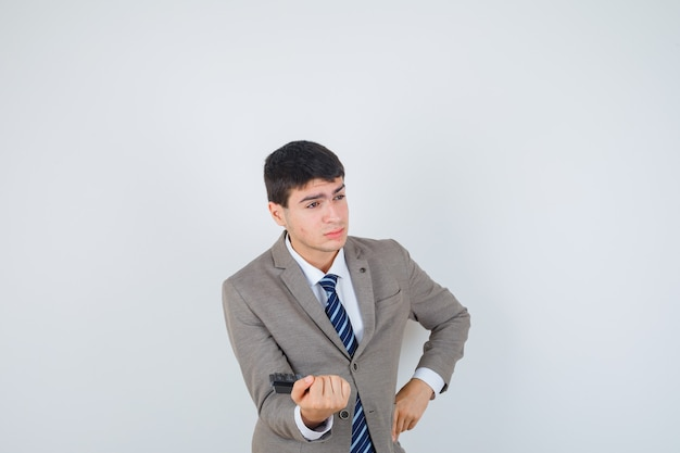 Young boy holding calculator, putting hand on hip in formal suit and looking pensive. front view.