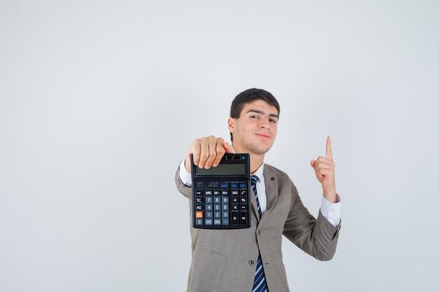 電卓を持って、フォーマルなスーツを着てユーレカのジェスチャーで人差し指を上げ、賢明に見える少年。正面図。