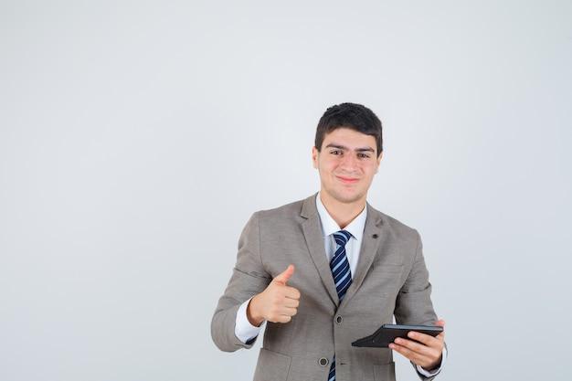 Мальчик держит калькулятор, показывает палец вверх в официальном костюме и выглядит счастливым, вид спереди.