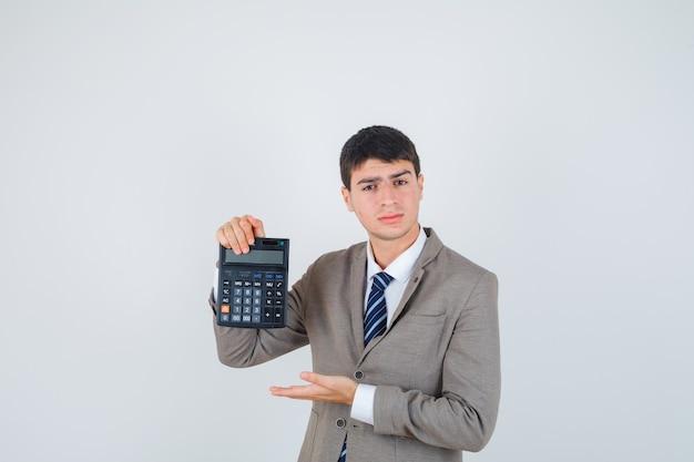 電卓を持って、フォーマルなスーツでそれを提示し、真剣に見えるように手を伸ばしている少年。正面図。
