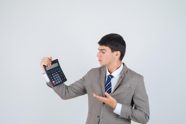 Молодой мальчик держит калькулятор, протягивая руку, представляя его в строгом костюме и серьезно выглядя. передний план.