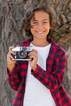 Young boy holding camera while outdoors with parents