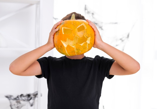 Young boy holding carved pumpkin