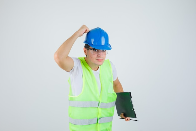 Мальчик держит доску сзажимом для бумаги и ручку, кладет руку на шлем в строительной форме и выглядит серьезным, вид спереди.