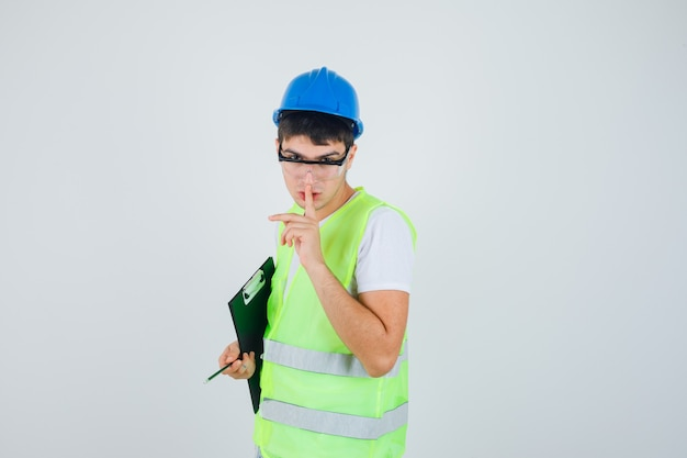 Young boy holding clipboard and pen, showing silence gesture in construction uniform and looking serious , front view.