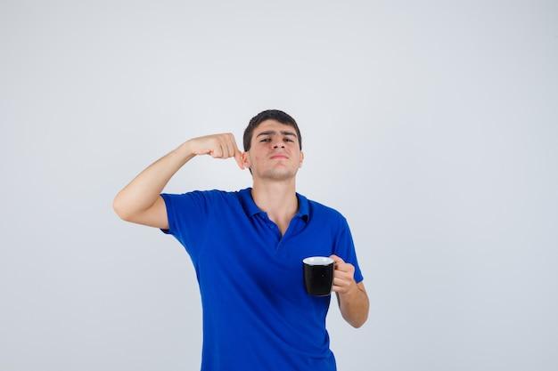 턱 근처 컵을 들고 어린 소년, 파란색 티셔츠에 주먹을 떨림과 자신감, 전면보기를 찾고.