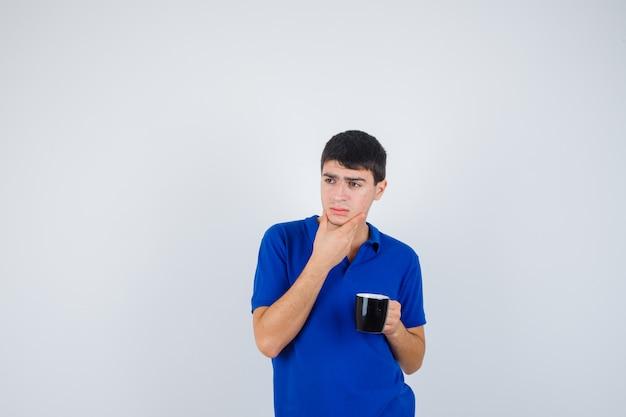あごの近くにカップを持って、青いtシャツで手のひらにあごをもたれ、物思いにふける少年。正面図。