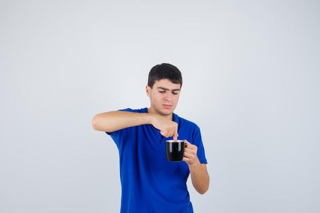 Giovane ragazzo che tiene la tazza vicino al mento, mettendoci la mano in maglietta blu e guardando curioso, vista frontale.