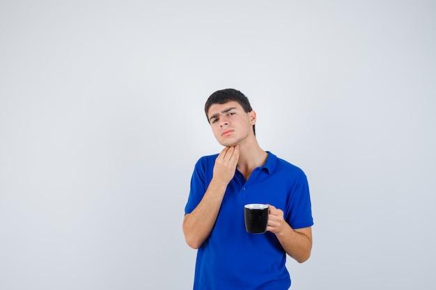 あごの近くにカップを持って、青いtシャツで気を引っ掻いて、物思いにふける、正面図を探している少年。