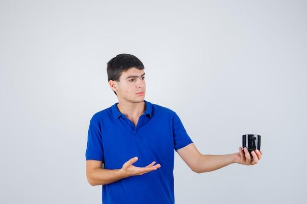 Giovane ragazzo che tiene la tazza, allungando la mano verso di essa in maglietta blu e guardando serio
