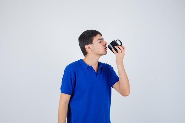 Молодой мальчик держит чашку, пытается выпить из нее жидкость в синей футболке и выглядит серьезным