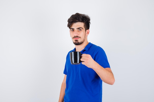 Giovane ragazzo che tiene tazza con la mano in maglietta blu e sembra serio. vista frontale.