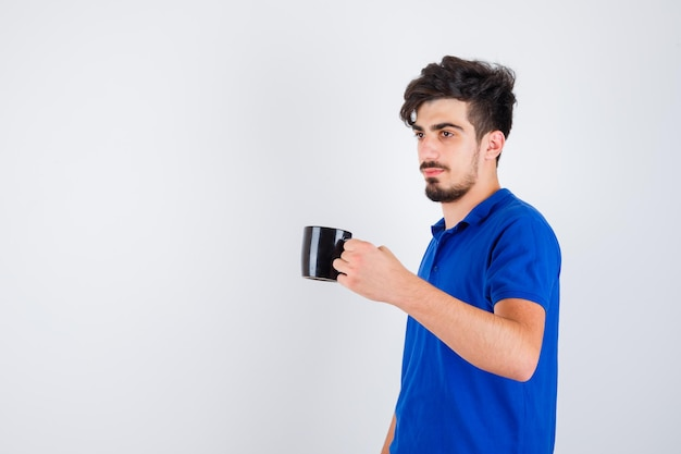 Young boy holding cup with hand in blue t-shirt and looking serious. front view.