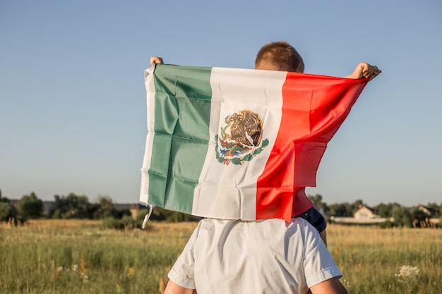 Young boy holding flag of mexico.