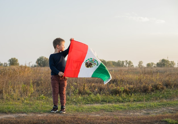 Young boy holding flag of mexico
