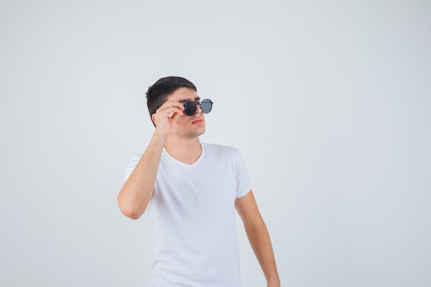 Young boy holding glasses, looking aside in t-shirt and looking cool , front view.
