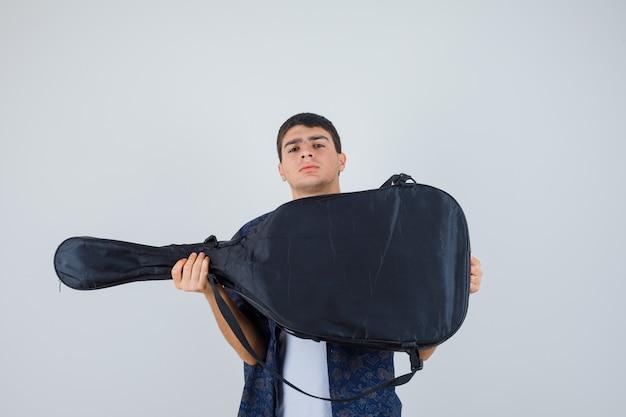 Tシャツにギターを持って自信を持って見える少年。正面図。