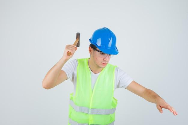 건설 유니폼에 망치를 들고 집중 찾고 어린 소년. 전면보기.