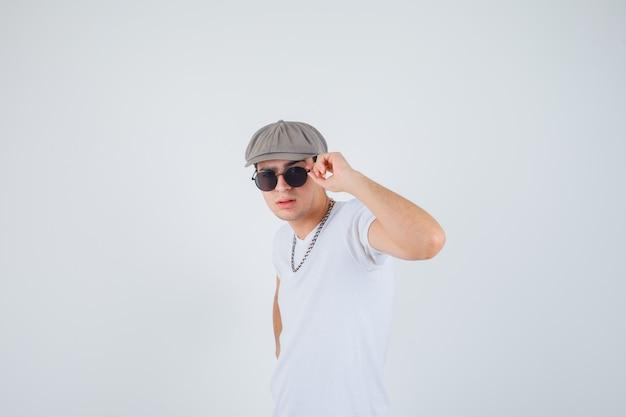 T- 셔츠, 모자에 안경에 손을 잡고 멋진 찾고 어린 소년. 전면보기.