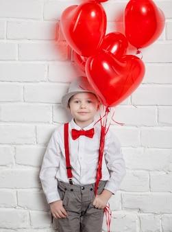 Young boy holding a heart-shaped ballon