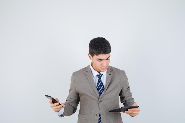 Молодой мальчик держит телефон, глядя на калькулятор в строгом костюме и глядя сосредоточенно, вид спереди.