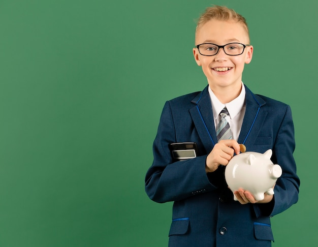 Young boy holding piggy bank