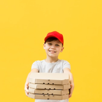 Young boy holding pizzas boxes
