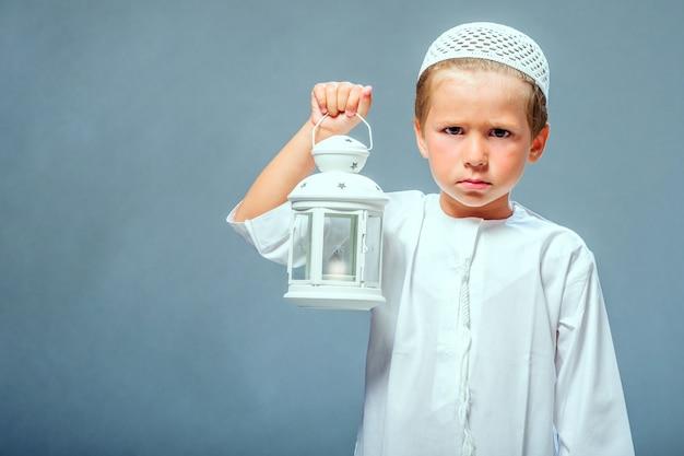 Мальчик держит фонарь рамадан
