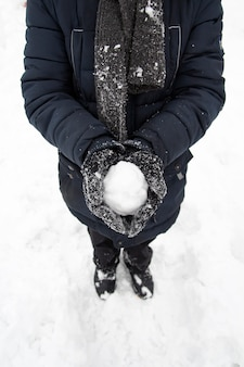 Young boy holding a snowball in her hands in the winter park