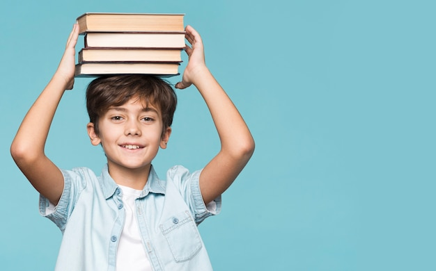 Young boy holding stack of books on head