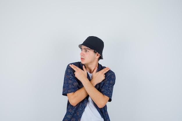 어린 소년 두 손을 잡고 넘어, 흰색 티셔츠, 꽃 무늬 셔츠, 모자에 총 제스처를 보여주는 자신감을 찾고. 전면보기.