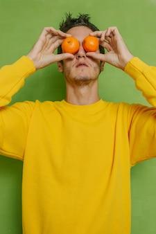 Молодой мальчик держит два апельсина в глазах на зеленом фоне, вертикальное фото