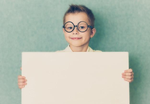 Молодой мальчик держит белую пустую доску на синем