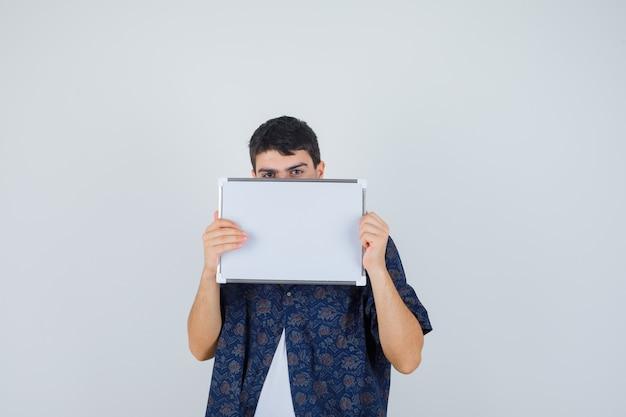 ホワイトボードを持って、白いtシャツ、花柄のシャツでその後ろに顔を隠し、真剣に見える少年、正面図。