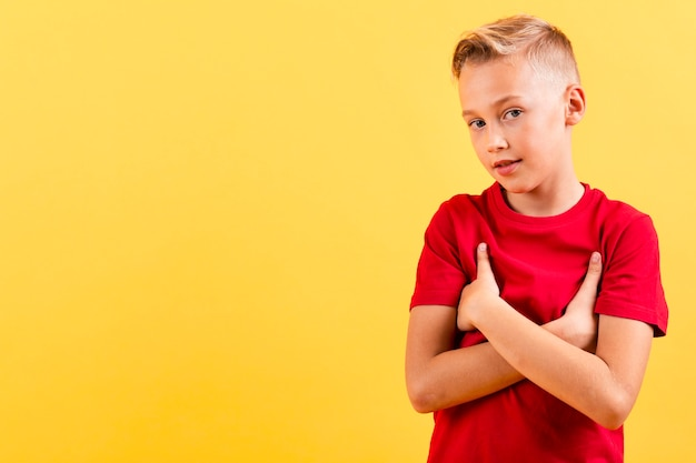 Young boy holding with arms crossed