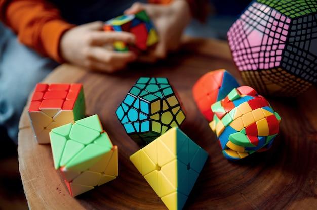어린 소년은 다채로운 퍼즐 큐브를 손에 들고 있습니다. 두뇌 및 논리적 마인드 훈련, 창의적인 게임, 복잡한 문제 해결을 위한 장난감