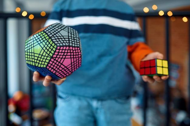 Мальчик держит в руках кубики головоломки. игрушка для тренировки мозга и логического мышления, творческой игры, решения сложных задач.
