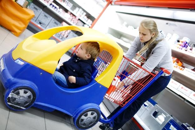 어린이 친화적 인 슈퍼마켓 트롤리에 어린 소년