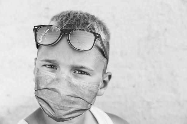 의료 마스크에 어린 소년입니다. 흑백 사진