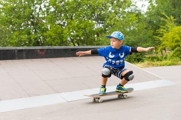 トレンディな青い服と安全装備を身に着けた少年が、伸ばした腕でボード上でスケートボードのバランスを練習しています