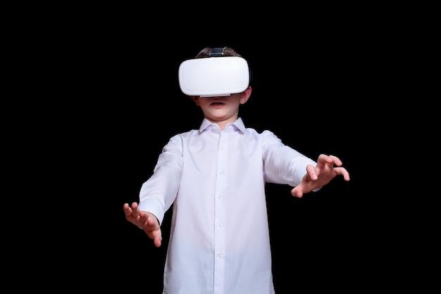 가상 현실 헬멧에 어린 소년입니다. 흰 셔츠. 검정색 배경
