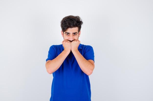 주먹을 물고 심각한, 전면보기를 찾고 파란색 티셔츠에 어린 소년.