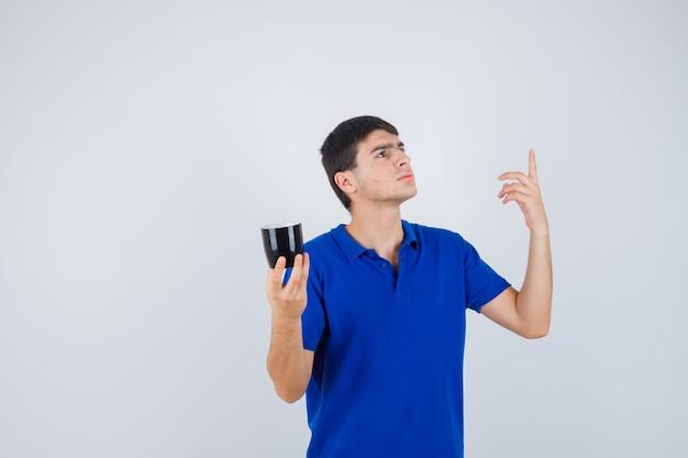 Молодой мальчик в синей футболке держит чашку возле подбородка, поднимает указательный палец в жесте эврики и выглядит разумно, вид спереди.