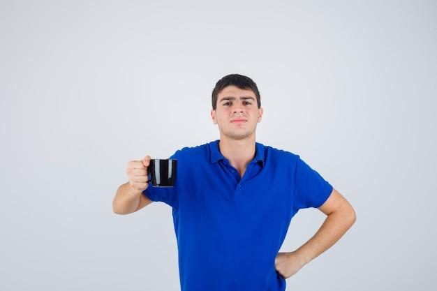 파란색 티셔츠 들고 컵에 어린 소년, 허리에 손을 넣어 자신감, 전면보기를 찾고.