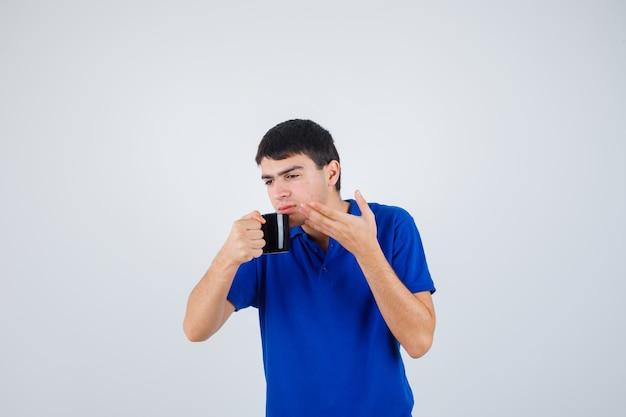 파란색 티셔츠 들고 컵에 어린 소년, 그것에서 액체를 마시고 초점을 맞춘 찾고, 전면보기.