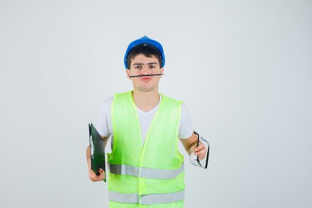 클립 보드 및 안전 안경을 손에 들고, 입으로 펜을 들고 심각한, 전면보기를 찾고 건설 제복을 입은 어린 소년.